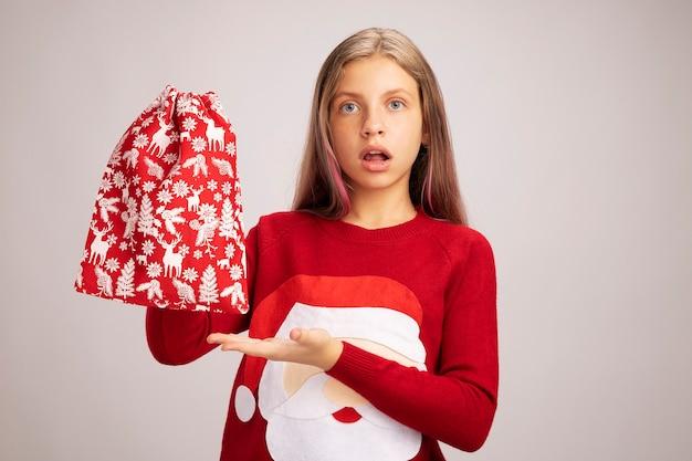 Bambina in maglione di natale che tiene in mano una borsa rossa di santa con regali che la presenta con il braccio della mano che sembra confusa in piedi su sfondo bianco