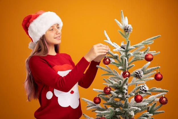 Bambina in maglione natalizio e cappello da babbo natale appesi giocattoli su un albero di natale sorridendo allegramente su sfondo arancione
