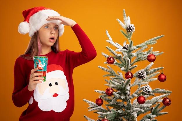 Bambina in maglione di natale e cappello della santa che tiene tazza di carta colorata che guarda lontano accanto a un albero di natale su sfondo arancione