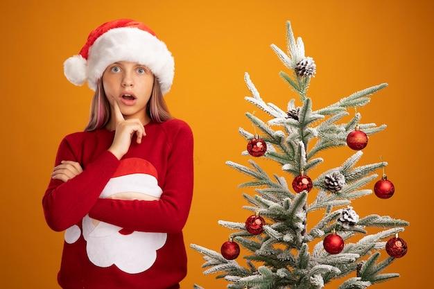 Bambina in maglione natalizio e cappello da babbo natale che guarda la telecamera stupita e sorpresa in piedi accanto a un albero di natale su sfondo arancione