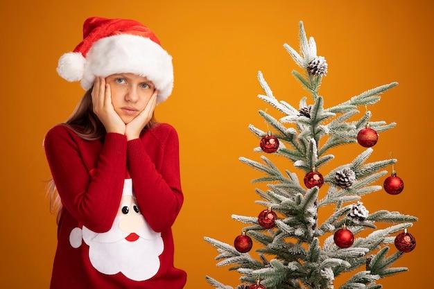 Bambina in maglione natalizio e cappello da babbo natale che guarda la telecamera confusa e dispiaciuta in piedi accanto a un albero di natale su sfondo arancione