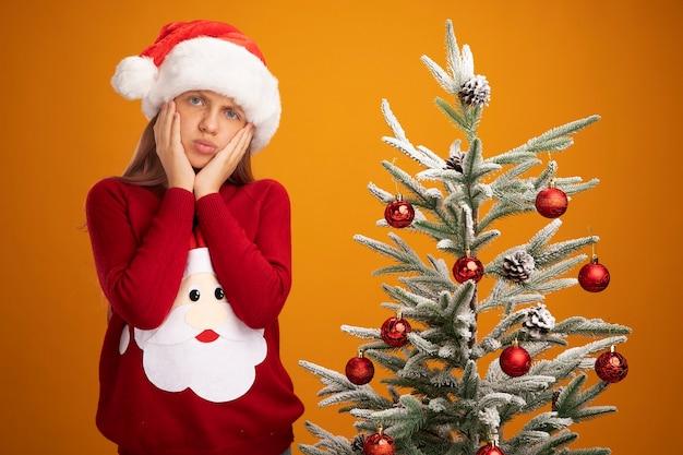 Bambina in maglione natalizio e cappello da babbo natale che guarda la telecamera confusa e preoccupata in piedi accanto a un albero di natale su sfondo arancione