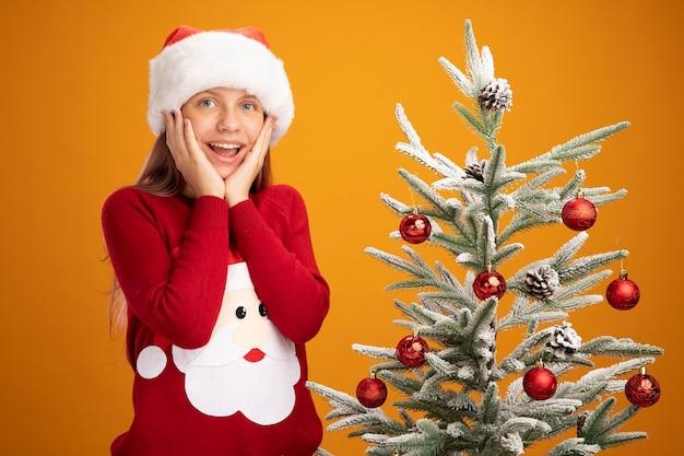 Bambina in maglione di natale e cappello di babbo natale che guarda l'obbiettivo felice ed eccitata in piedi accanto a un albero di natale su sfondo arancione