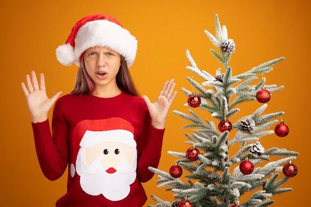 Bambina in maglione di natale e cappello di babbo natale guardando la telecamera alzando le braccia con espressione delusa in piedi accanto a un albero di natale su sfondo arancione orange
