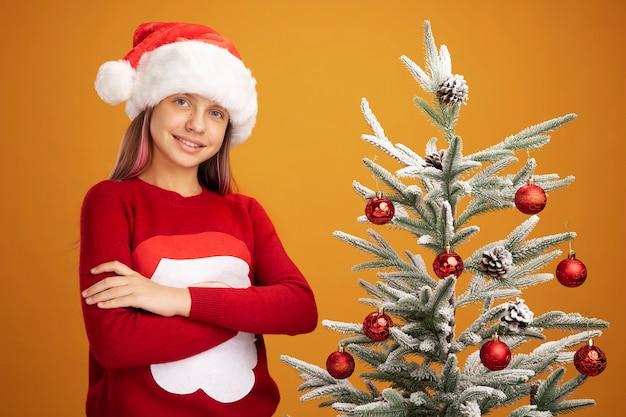 Bambina in maglione di natale e cappello di babbo natale che guarda l'obbiettivo sorridente fiducioso in piedi accanto a un albero di natale su sfondo arancione