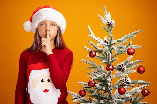 Bambina in maglione di natale e cappello di babbo natale che guarda l'obbiettivo con faccia seria facendo gesto di silenzio con il dito sulle labbra in piedi accanto a un albero di natale su sfondo arancione