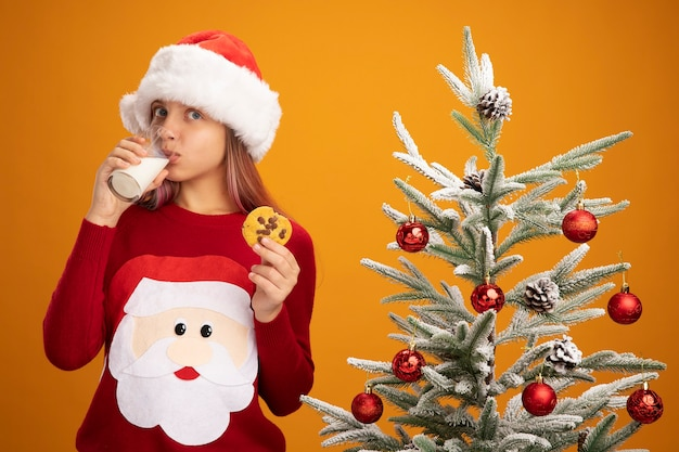 Little girl in christmas sweater and santa hat with glass of milk and cookie drinking milk standing next to a christmas tree over orange background