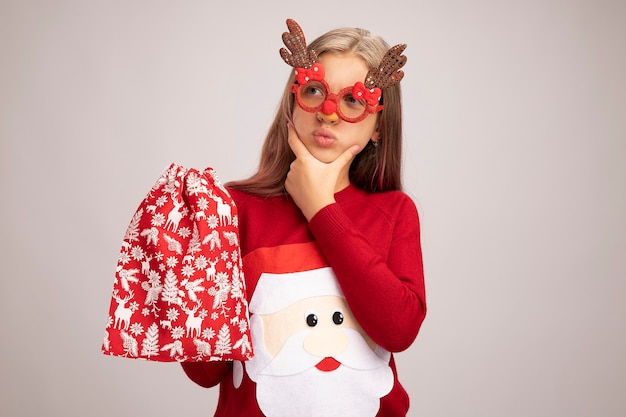 Little girl in christmas sweater wearing funny party glasses holding santa red bag with gifts looking aside puzzled standing over white background