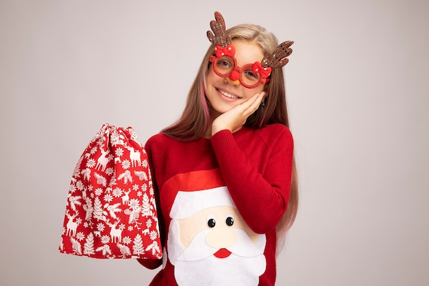 Little girl in christmas sweater wearing funny party glasses holding santa red bag with gifts looking at camera happy and positive smiling standing over white background