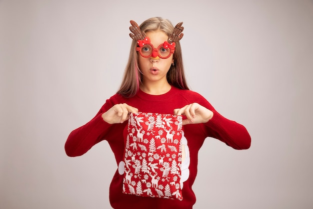 Little girl in christmas sweater wearing funny party glasses holding santa red bag with gifts looking at camera surprised standing over white background