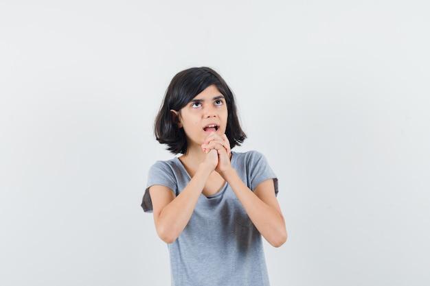 Маленькая девочка, взявшись за руки в молящемся жесте в футболке и выглядя обнадеживающей, вид спереди.