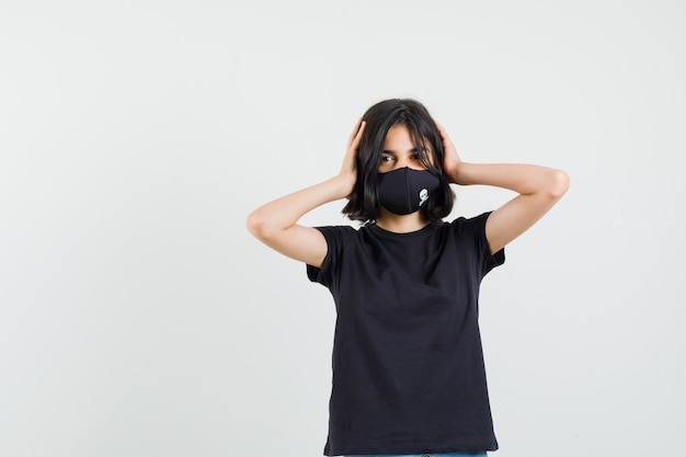 Little girl clasping head in hands in black t-shirt, mask and looking happy. front view.