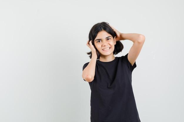 Маленькая девочка обхватив голову руками в черной футболке и выглядела счастливой, вид спереди.