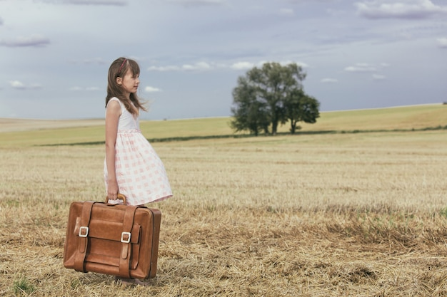 Little girl in classic dress with travel suitcase