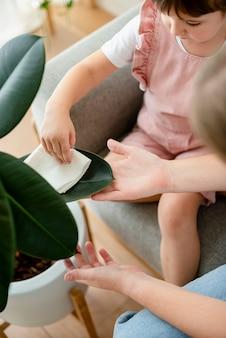 Bambina che pulisce la foglia della pianta in vaso