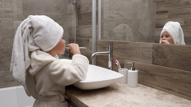 Little girl cleaning teeth in bathroom against mirror