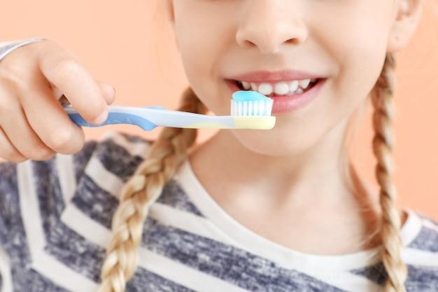 Маленькая девочка чистит зубы на бежевом