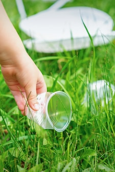 Little girl cleans plastic utensils on the green grass in the park