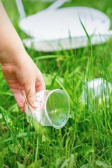 Маленькая девочка чистит пластиковую посуду на зеленой траве в парке