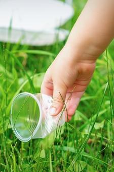 Маленькая девочка чистит пластиковую посуду