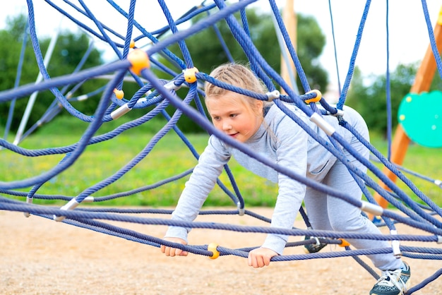冒険公園に登る少女。女の子はロープコースの冒険に登るのが大好きです。ロープ障害物コースの少女。