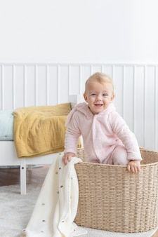 Little girl climbing in a laundry basket