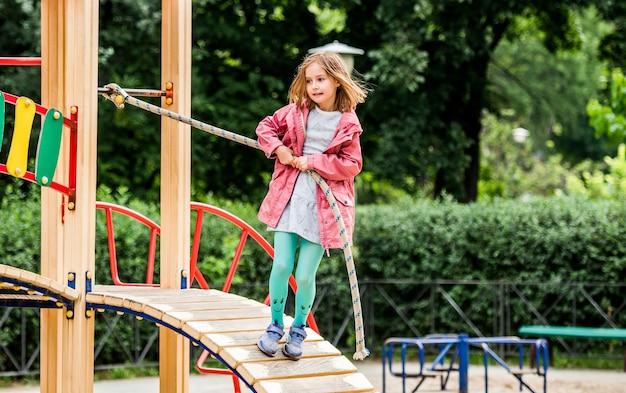 少女が公園で子供の遊び場でロープを登る