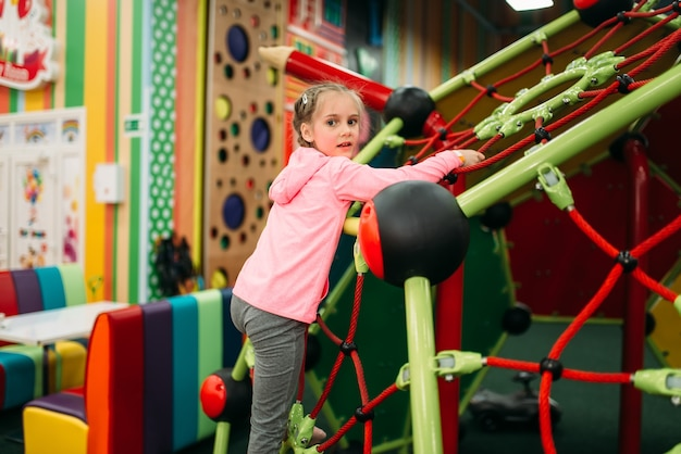Little girl climbing on a ropes on playground in childrens entertainment center. child sport activity. happy childhood