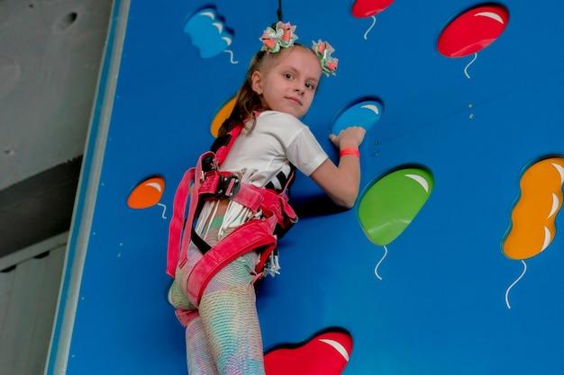 공기 풍선 구멍을 잡고 파란색 벽을 등반하는 어린 소녀. 밧줄. 어린이들. 운동장