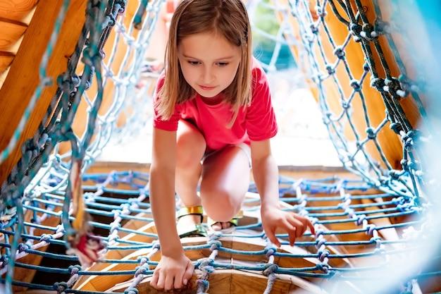 公園の遊び場でネットを登る少女