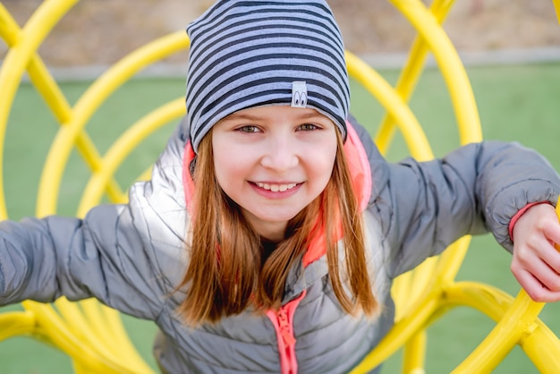 Маленькая девочка взбирается на детские желтые аттракционы на детской площадке. портрет крупным планом