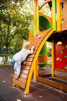 A little girl climbs the climbing wall on the children's slide on the playground.