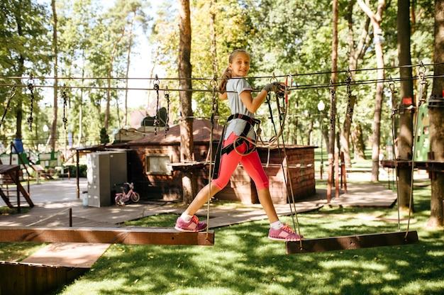 Маленькая девочка поднимается в веревочном парке