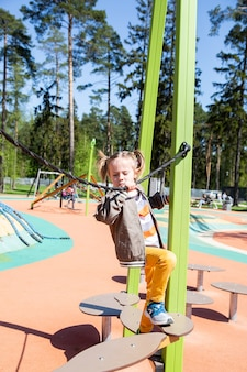 Little girl climbs the suspension bridge at the playground outdoors