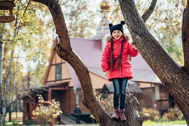 Little girl climbs a tree