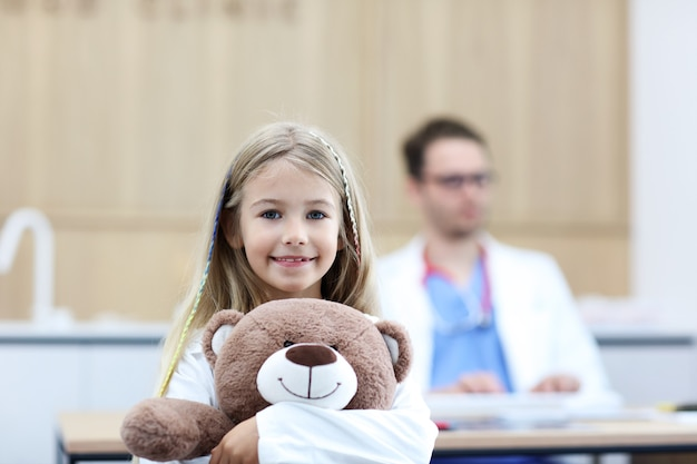 Little girl in clinic with pediatrician in the background