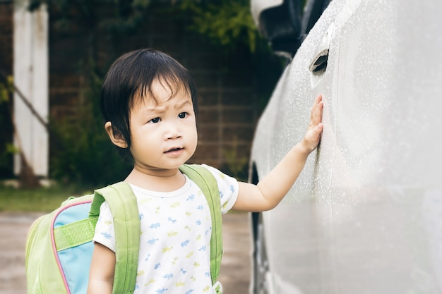 Little girl close the car door for to school. child playing outdoors in school.