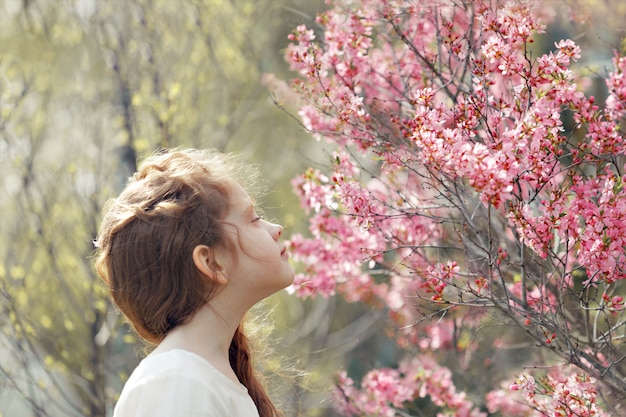 Little girl closed her eyes and breathes the aroma of a flowering tree.