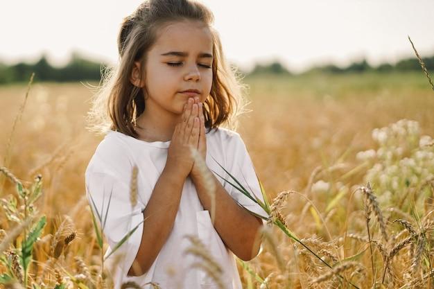 Маленькая девочка закрыла глаза, молясь в поле пшеницы. руки сложены в молитве. концепция религии