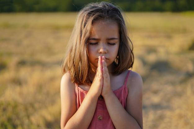 어린 소녀는 필드에서기도하면서 그녀의 눈을 감았 다.