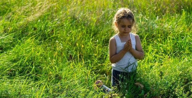 少女は目を閉じ、野外で祈り、信仰、霊性、宗教の祈りの概念に手を組んだ。平和、希望、夢のコンセプト。