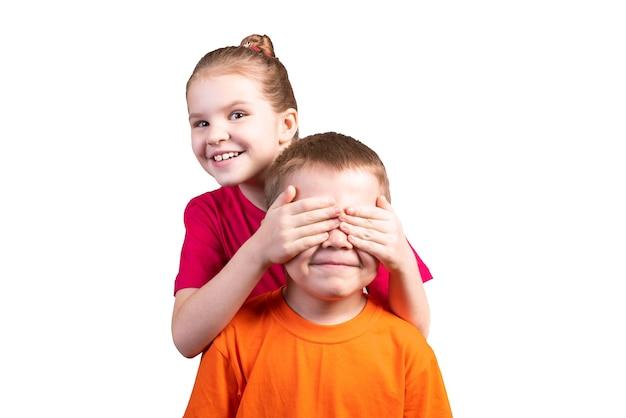 小さな女の子は手のひらで男の子の目を閉じます。白い背景で隔離。あらゆる目的のために。