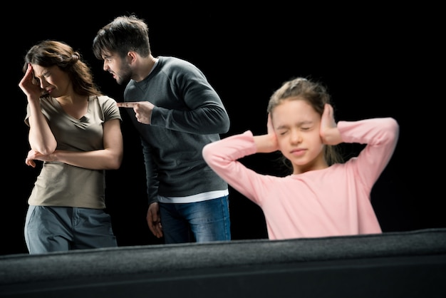 Little girl closing ears while parents quarreling