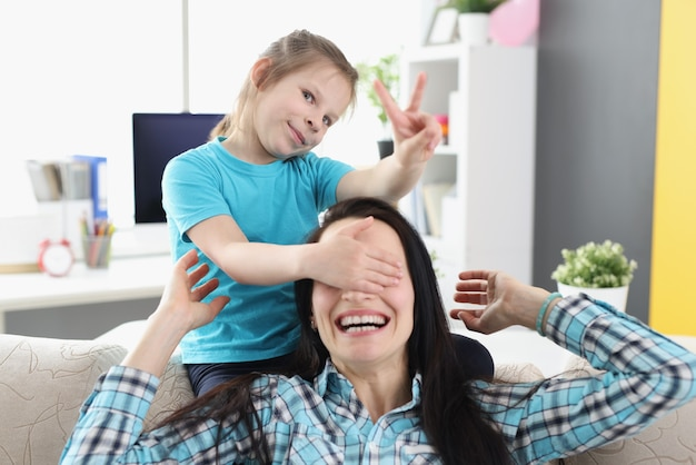 家で笑顔の母親の目を閉じる少女