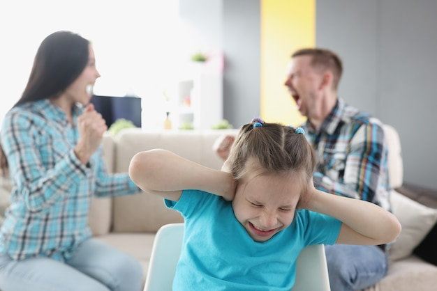 Little girl closing her ears against background of swearing parents at home