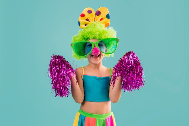 Little girl in clown costume with pom poms