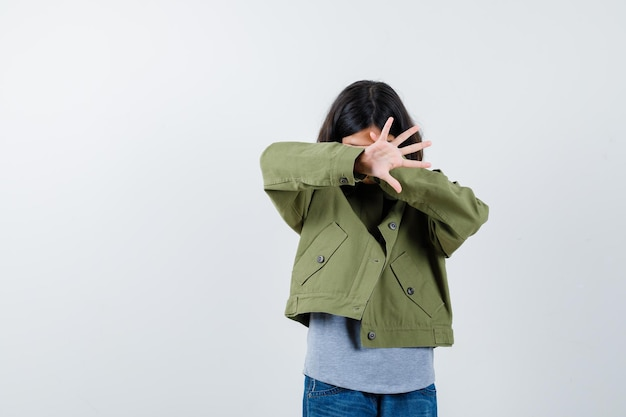 Little girl in coat, t-shirt, jeans covering eyes with hand, showing palm and looking scared , front view.