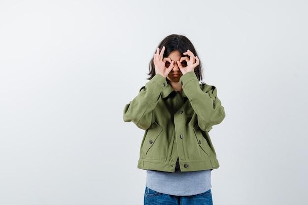 Bambina in cappotto, t-shirt, jeans che mostra il gesto degli occhiali e sembra carina, vista frontale.