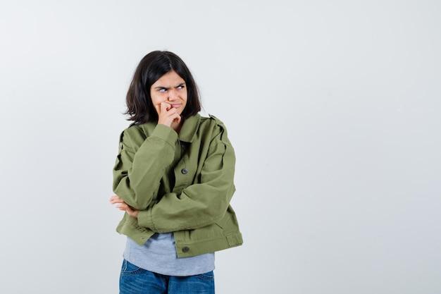 Bambina in cappotto, t-shirt, jeans in piedi in posa di pensiero e guardando premurosa, vista frontale.