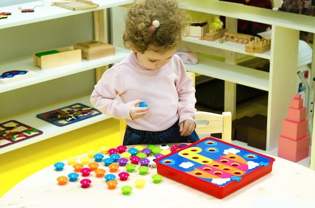 Little girl collects a puzzle.